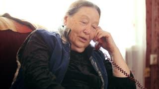 Friendly old Woman pensioner speaks phone, telephoto