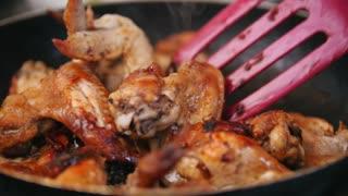 Frying Chicken wings preparing in pan - spatula stirring food