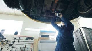 Garage auto service - mechanic checks the bottom of the lifted car, small business