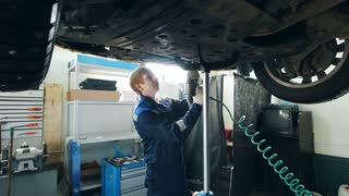 Garage auto service - mechanic unscrewing the bottom of the lifted car, small business