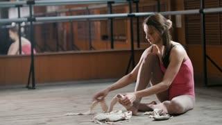 Girl balerina dancer putting on her ballet shoes
