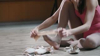 Girl ballet dancer putting on her ballet shoes