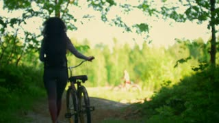 Girl cyclist meets her friend in a clearing in the woods, Sunny summer day