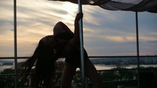 Girl dancing on a pole, dancer fitness model - outdoor performance, slow-motion