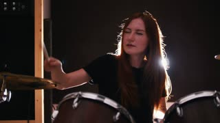 Girl drummer playing drums with her eyes closed