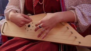 Girl in Russian folk costume playing vintage musical instrument - the gusli