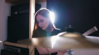 Girl is very diligent musician plays drums