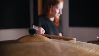 Girl-musician hits a stick on a drum
