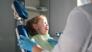 Girl on reception at the dentist, the stomatologist cleaning and watering the child's teeth, girl smiling and talking