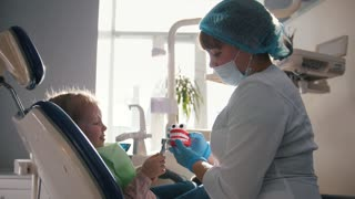 Girl on reception at the dentist, the stomatologist examines the child's teeth, cute and naughty girl smiling