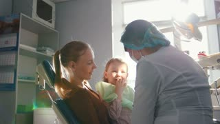 Girl on reception at the dentist, the stomatologist examines the child's teeth, naughty girl smiling