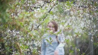Girl runs making her way through cherry branches, summer day, slow-motion