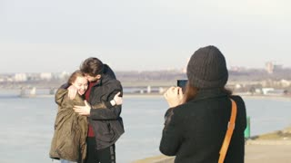 Girl takes a photo for her friends couple at the walk on the waterfront
