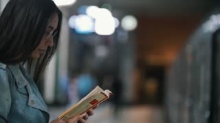 Girl waiting for her train and reading a book, slow motion