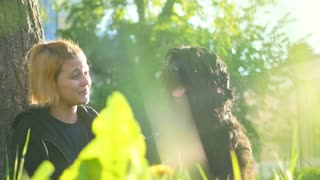 Girl with her Russian black Terrier sitting near a tree on the grass in the Park and stroking it