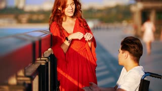 Girl With Red Hair And Guy On A Wheelchair Talking On The Waterfront On A Summer Evening