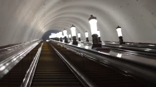Going down the escalator in the subway past the lamps. Dim lights