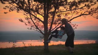 Grandmother and grandson at summer sunset play and grandmother helps her grandson climb a tree