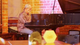 Gray-haired man with a tail on his head with glasses playing the piano in a jazz bar