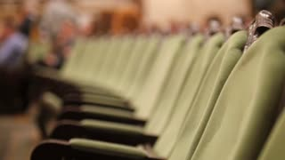 Green chairs without spectators - empty concert hall or theater