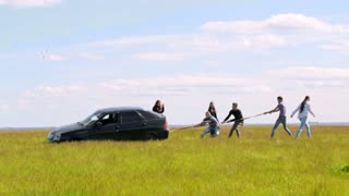 Group of friends pulls the car with a rope in summer field