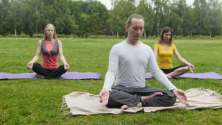Group of sportsmen performs breathing exercise outdoors in a green park