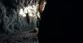 Group of young speleologists in helmets entered in the dark cave