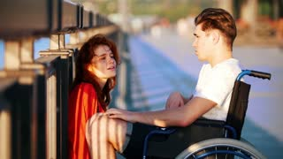 Guy On The Wheelchair Says Something To Red-Haired Girl And She Iistens Carefully, On Promenade In Summer Evening