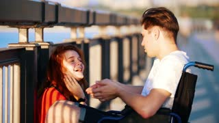 Guy On The Wheelchair Says Something To Red-Haired Girl And She Iistens Carefully, On Promenade
