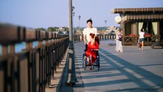 Guy Rolls A Disabled A Smiling Girl With The Red Hair In A Wheelchair On The Waterfront