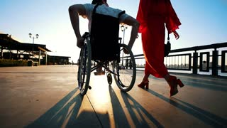 Guy With Diseased Legs On Wheelchair Walking With Girlfriend On The Waterfront In The Summer Evening
