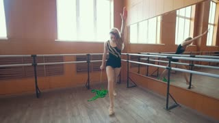 Gymnastic - young woman dancing with a green ribbon -training a gymnastics exercise, steadycam shot