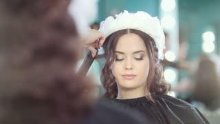 Hairdresser making curly hair for beautiful model