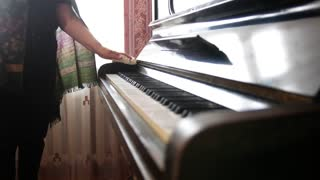 Hand of old woman at home wipes the dust on piano
