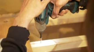 Hands of male screwing the bolt using electric screwdriver