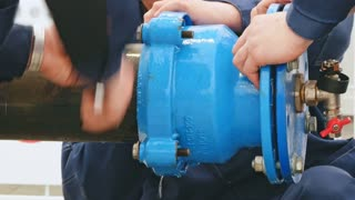 Hands of male workers are water pipes on water supply system