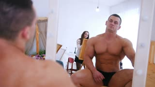 Handsome shirtless muscular guy is posing in front of the mirror for girls artists