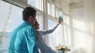 Happy cheerful loving couple making selfie on window, young attractive guy and girl