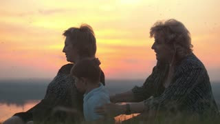 Happy family - grandmother, mother and son sitting on high hill at summer sunset