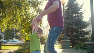 Happy father and son playing in summer park - slow-motion