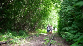 Happy teenagers running on abandoned railway in forest at sunny day