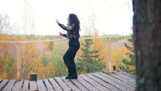 Happy woman dancing on platform. Forest on the background
