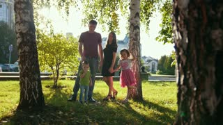Healthy family in a park at summer evening - father, mammy, daughter and little boy