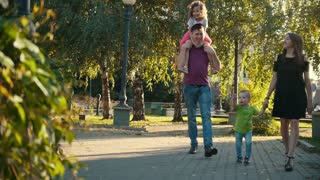 Healthy family walking in the park at summer evening - father, mammy, daughter and little boy, slow-motion