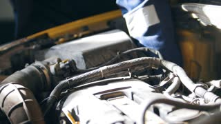 Hood of the car - the engine, the battery, the injector - mechanic working in the automotive service