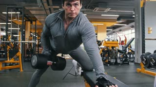 In the gym - athlete man lifting dumbbells