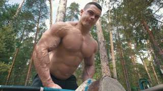Inflated muscular man picks up huge heavy kettlebell - workout in forest