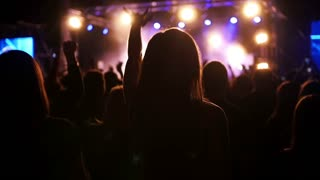 Jubilant crowd in the blue lights for a rock concert