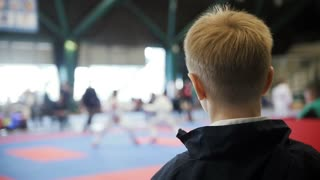 Karate championship - teenager boy looking at karate fighting - spectator at competition