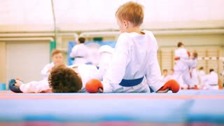 Karate children in white kimono and gloves lay on mats